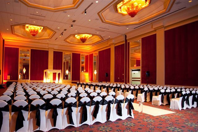 black sashes on white spandex chair covers lined up for a wedding at a hotel