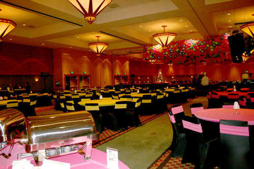 large conference room with black spandex chairs and neon yellow and pink sashes