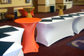 white spandex linens with an orange cocktail table